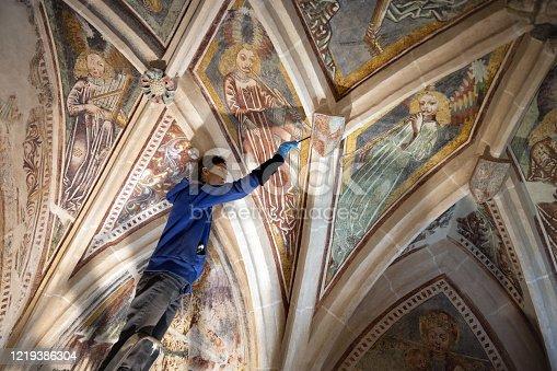 Female Artist Working on Restoration of Antique Chapel