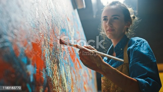 910798810 istock photo Female Artist Works on Abstract Oil Painting, Moving Paint Brush Energetically She Creates Modern Masterpiece. Dark Creative Studio where Large Canvas Stands on Easel Illuminated. Low Angle Close-up 1183183770