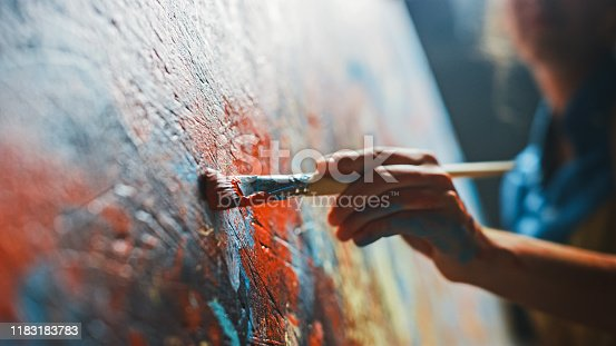 910798810 istock photo Female Artist Works on Abstract Oil Painting, Moving Paint Brush Energetically She Creates Modern Masterpiece. Dark Creative Studio where Large Canvas Stands on Easel Illuminated. Low Angle Close-up 1183183783