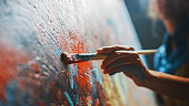 istock Female Artist Works on Abstract Oil Painting, Moving Paint Brush Energetically She Creates Modern Masterpiece. Dark Creative Studio where Large Canvas Stands on Easel Illuminated. Low Angle Close-up 1183183783