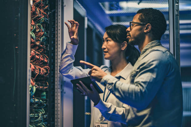 female asian it technician explaining network connection to a novice engineer - mainframe stock pictures, royalty-free photos & images