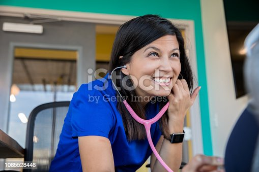 Female Asian nurse or doctor using a stethoscope while meeting with patient.  Doctor is wearing scrubs and sitting down.