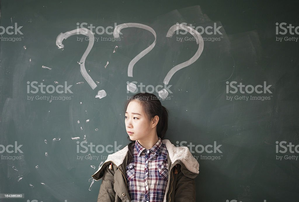 Female Asian student against chalkboard with question marks royalty-free stock photo