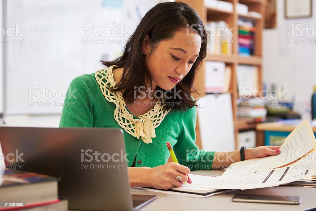 Female Asian teacher at her desk marking students' work stock photo