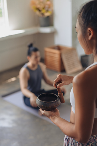 Female Asian yoga teacher conducting a meditation session with a singing bowl