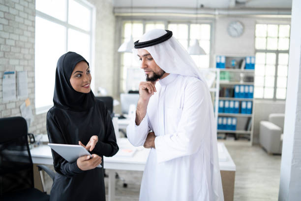 Female assistant discussing with arab businessman in modern office