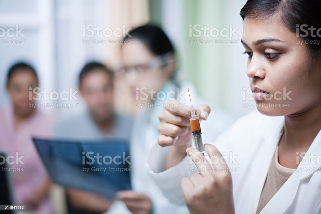 Female assistant doctor preparing injection in clinic. stock photo