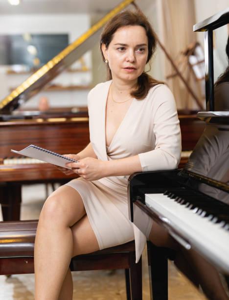 assistentin oder kundin im piano music store - klavier verkaufen stock-fotos und bilder
