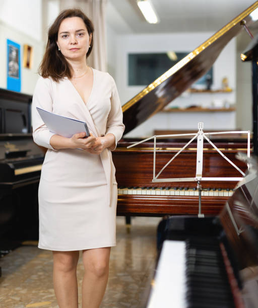 weibliche assistentin oder kundin im piano music store - klavier verkaufen stock-fotos und bilder