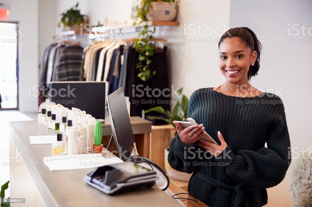 衣料品店では、カウンターから笑顔の女性アシスタント ストックフォト