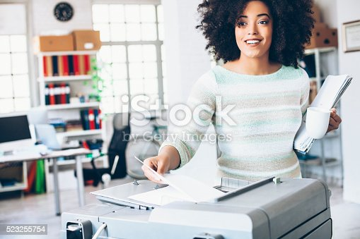 istock Female assistant using copy machine at workplace 523255754