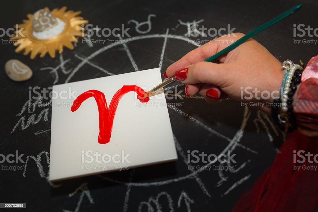 Female astrologer aries draws zodiac sign on white tile stock photo