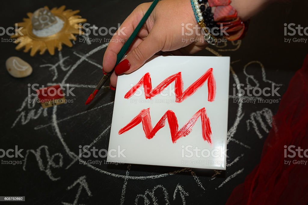 Female astrologer draws aquarius zodiac sign on white tile stock photo