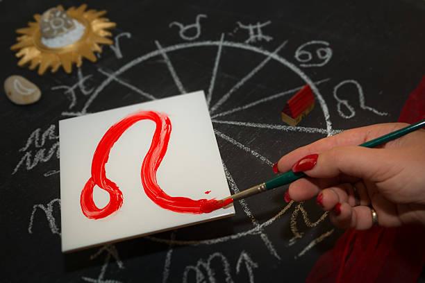 Female astrologer draws leo zodiac sign on white tile stok fotoğrafı