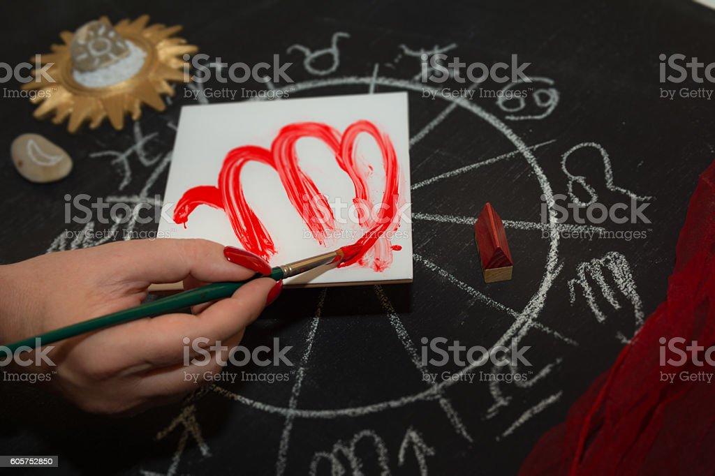 Female astrologer draws virgo zodiac sign on white tile stock photo