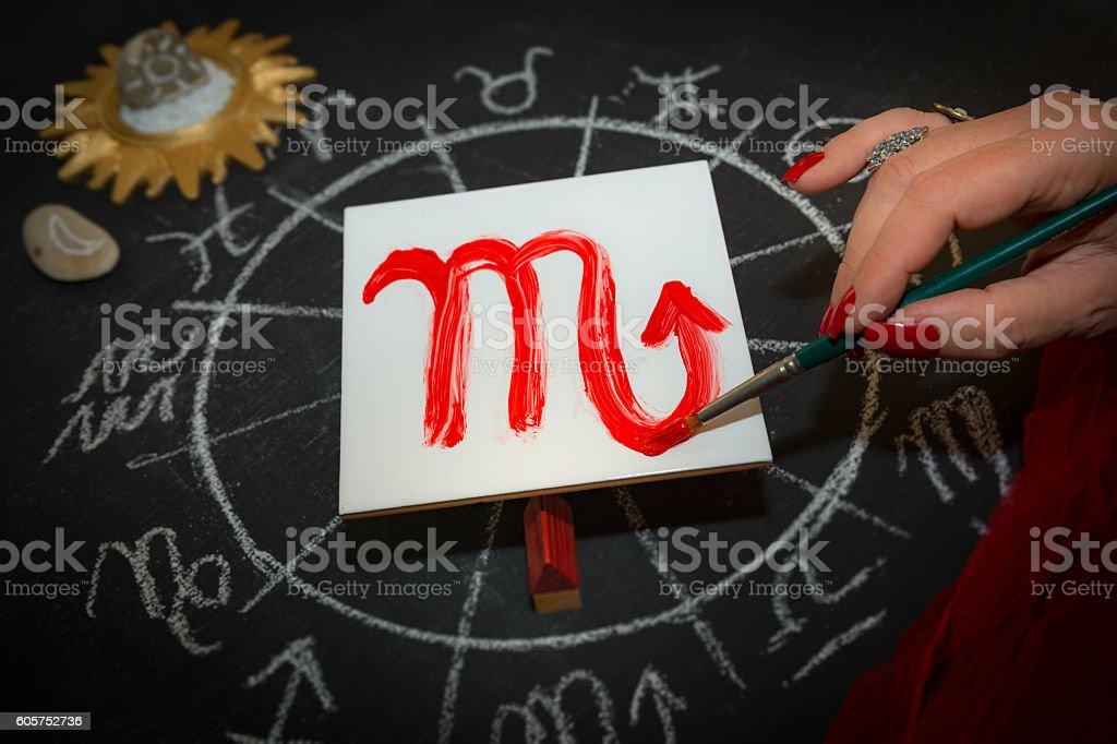 Female astrologer scorpio draws zodiac sign on white tile stock photo