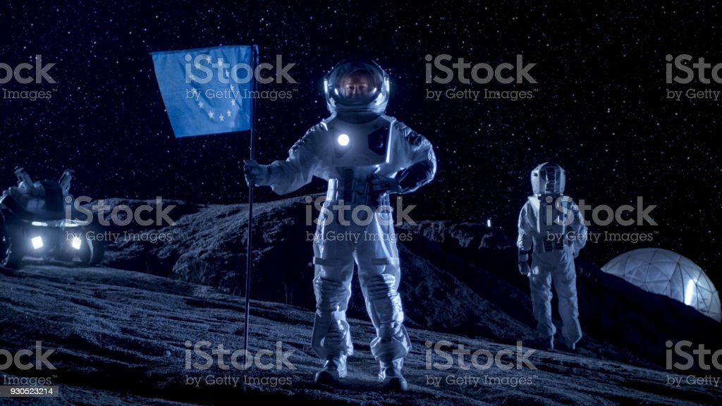 Female Astronaut Planting Flag of Europe Union on the Alien Planet. In the Background Her Crew Member, Living Station and Exploration Rover. Space Travel and Solar System Colonization Concept. stock photo