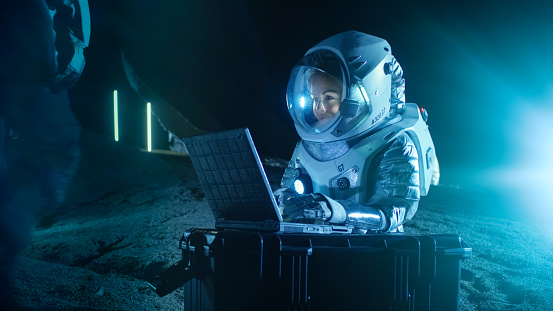 Female Astronaut Wearing Space Suit Works on a Laptop, Exploring Newly Discovered Planet, Communicating with the Earth. In the Background Her Crew Member and Space Habitat. Colonization Concept.