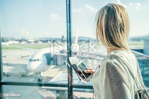 Young woman in airport waiting for flight sitting on bench with phone and passport in hands