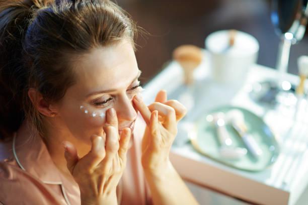 female at modern home in sunny winter day applying eye cream stock photo