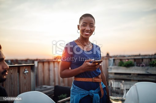 Beautiful young african woman with bald head standing on roof holding her mobile phone. Female at rooftop party with phone at sunset.