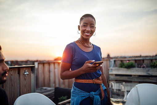 istock Female at rooftop party with phone 1045996804