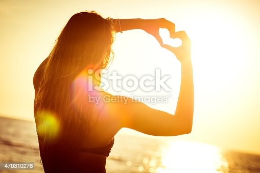 Young woman at the beach, making the shape of a heart with her hands, towards the sun.