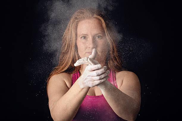 Female Athlete Apllying Chalk Clap To Hands. Sportswoman Preparing Determination stock photo