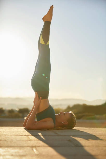 Female athlete balancing while doing Sarvangasana Side view of female athlete balancing while doing Sarvangasana. Full length of young woman is practicing yoga on footpath. She is exercising on sunny day at park. shoulder stand stock pictures, royalty-free photos & images