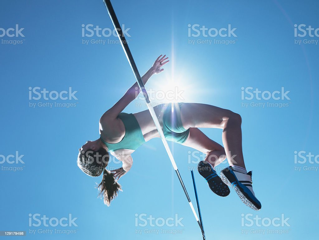 Female athlete clearing high jump stock photo