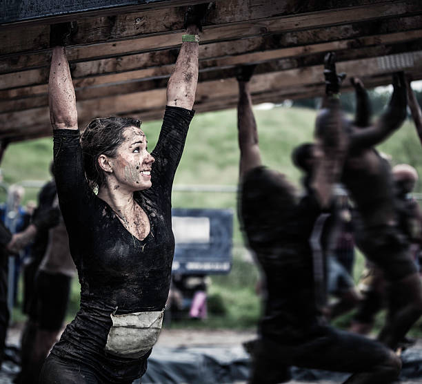 Female athlete competing in an obstacle course Young woman on monkey bars covered in mud. obstacle course stock pictures, royalty-free photos & images