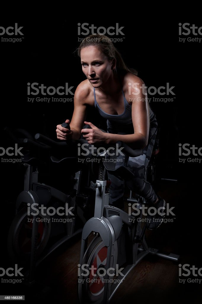 Female Athlete Cycling in Gym stock photo