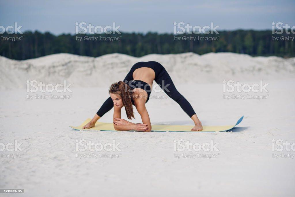 Female athlete doing a warm up on yoga mat. stock photo