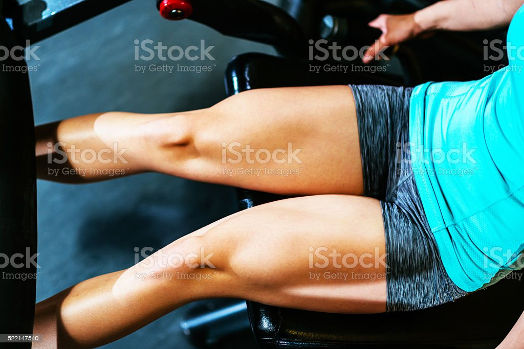 Female athlete doing squats in gym for buttocks and legs stock photo