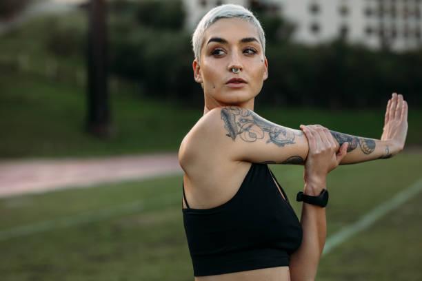 dabei strecken ihren arm training sportlerin - tattoos frauen arm stock-fotos und bilder