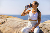 istock Female Athlete Drinking Water During Outdoor Workout by the Sea 1315678912
