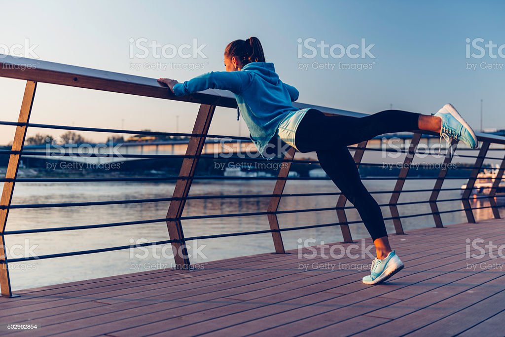 Female athlete exercising by the river stock photo
