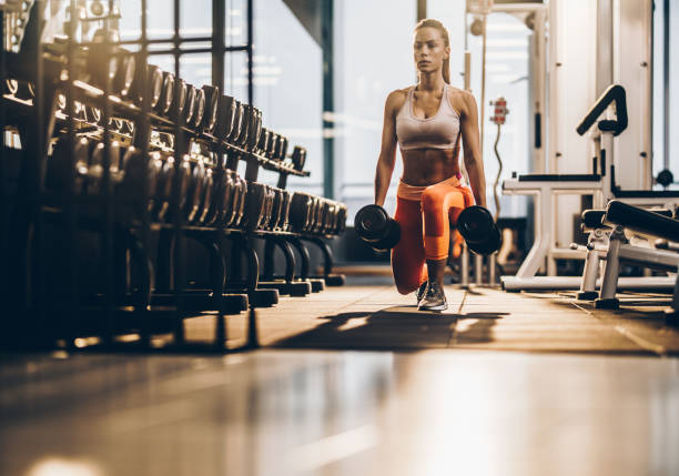 female athlete exercising with dumbbells in a lunge position at gym. - dumbbell stock pictures, royalty-free photos & images