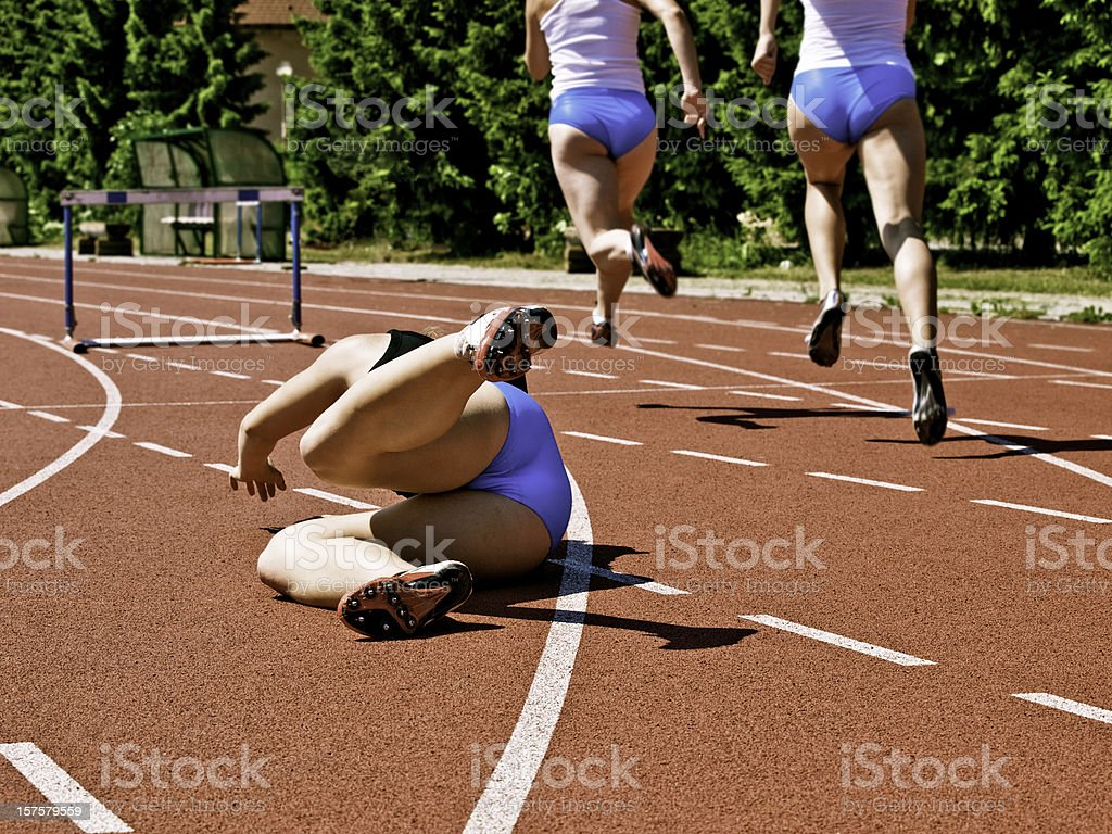 Female athlete falling down on track race stock photo