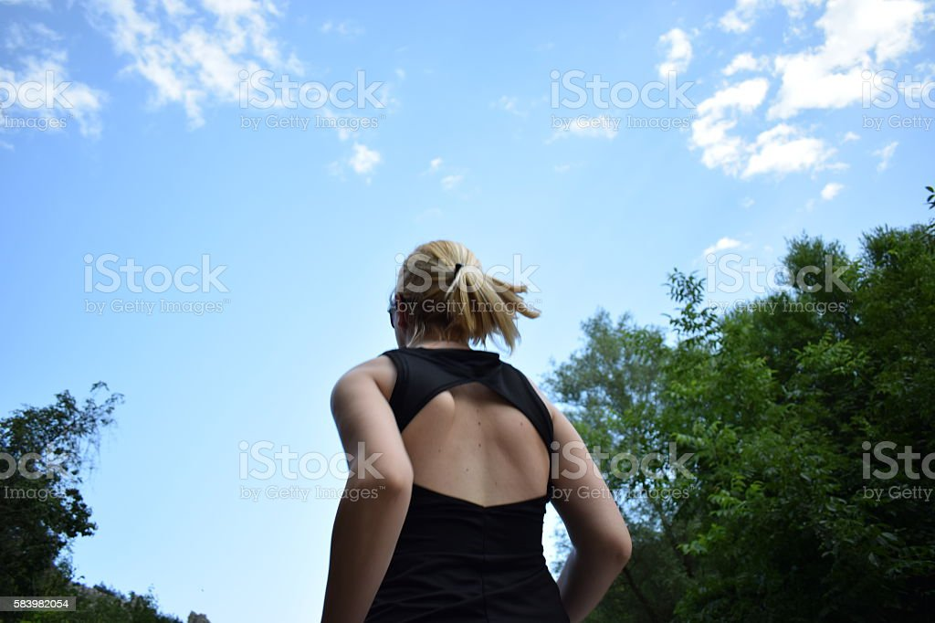 Female athlete from behind on outdoor run stock photo
