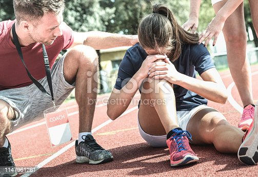 istock Female athlete getting injured during athletic run training - Male coach taking care on sport pupil after physical accident - Team care concept with young sporty people facing mishaps casualty 1147961261