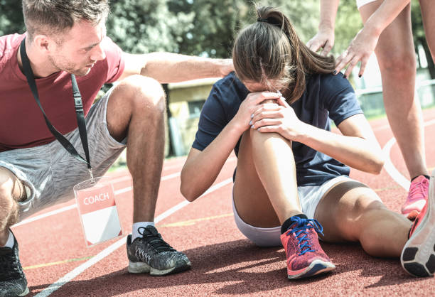 female athlete getting injured during athletic run training - male coach taking care on sport pupil after physical accident - team care concept with young sporty people facing mishaps casualty - lesionato foto e immagini stock