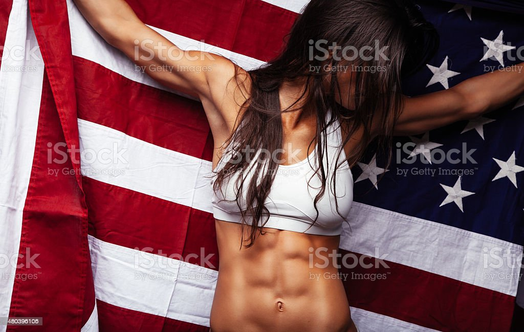 Female athlete holding American Flag stock photo