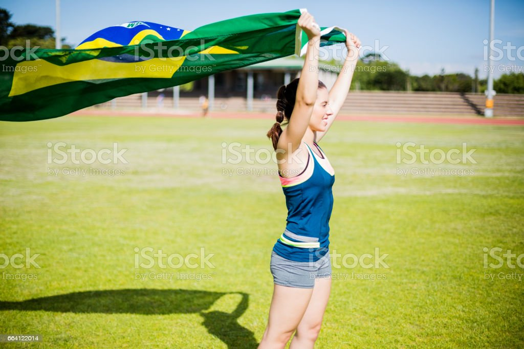 Female athlete holding an Brazilian flag foto stock royalty-free