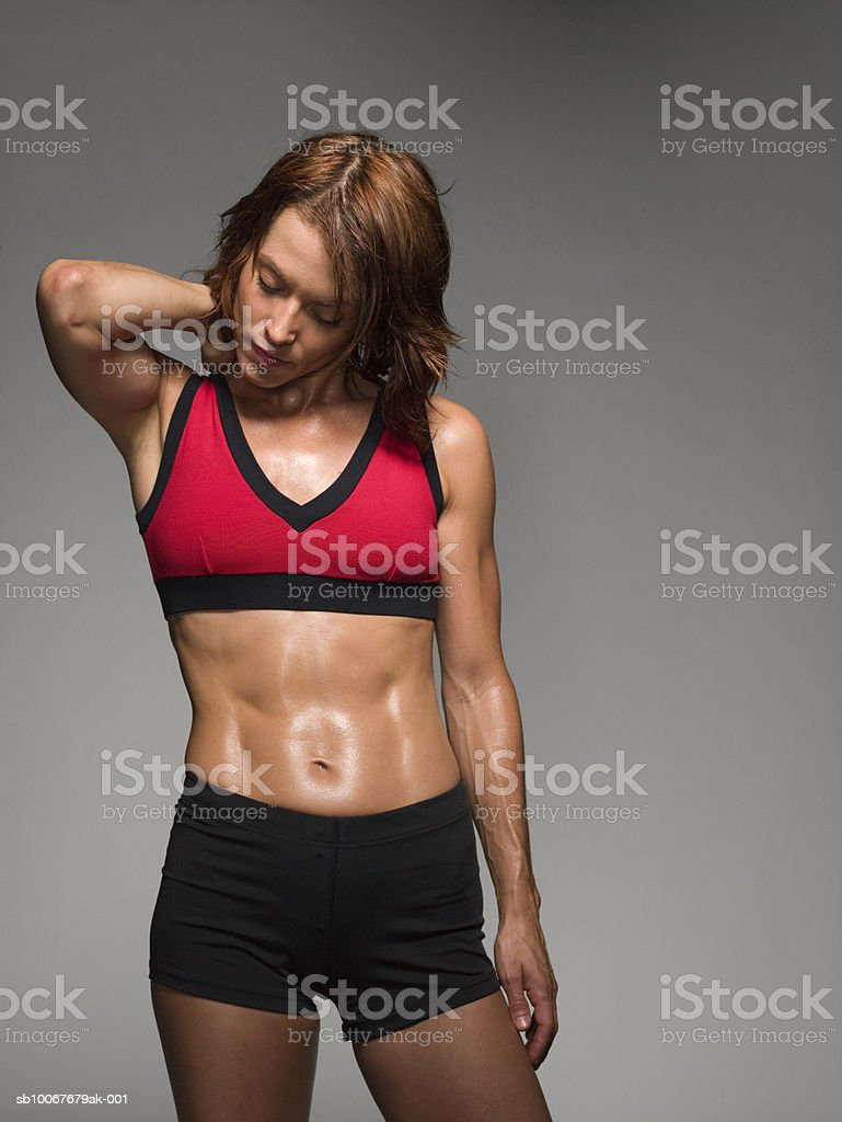 Female athlete holding neck, studio shot royalty free stockfoto