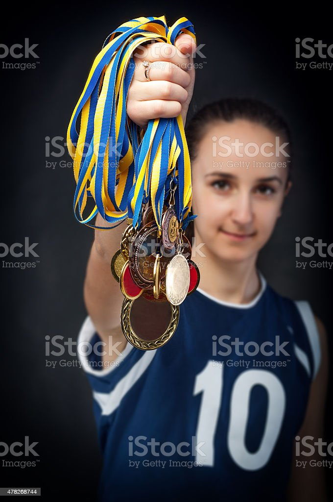 female athlete holds in hands bunch of medals stock photo