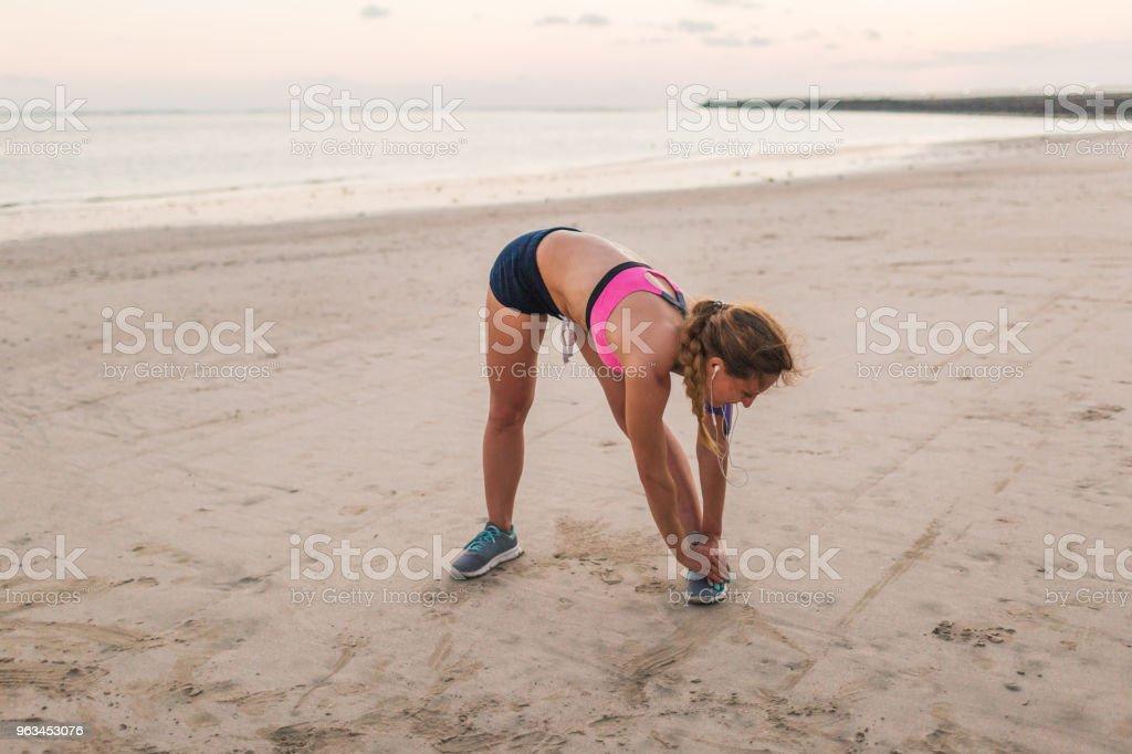 kadın atlet plajda egzersiz yaparak kulaklık - Royalty-free Aktif Hayat Tarzı Stok görsel