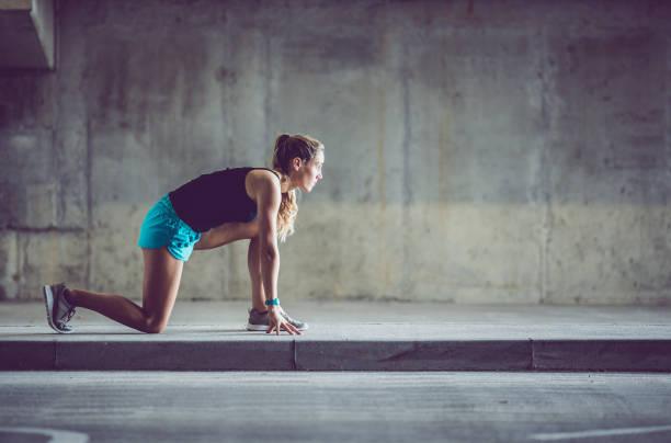 sportlerin in niedrigen startposition auf einer städtischen straße - joggerin stock-fotos und bilder