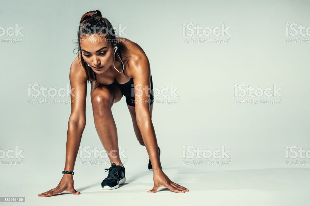 Atleta femenina en posición de arranque listo para competencia - foto de stock