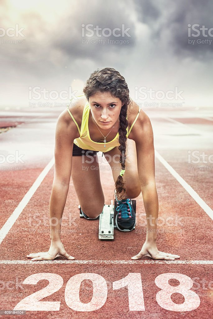 Female athlete in the starting blocks stock photo